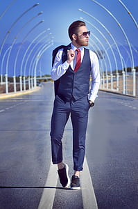 man standing on middle of road wearing dress shirt and pants
