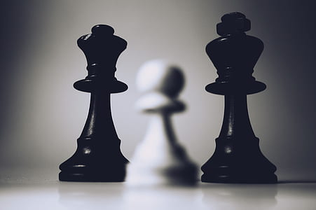 selective-focus photography of two black chess pieces beside white chess piece