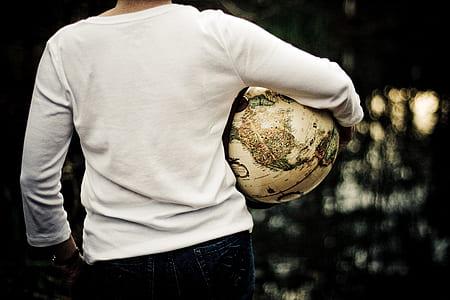 man wearing white long-sleeved shirt carrying globe