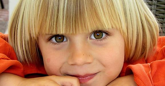 child with blonde hair wearing orange long-sleeved shirt