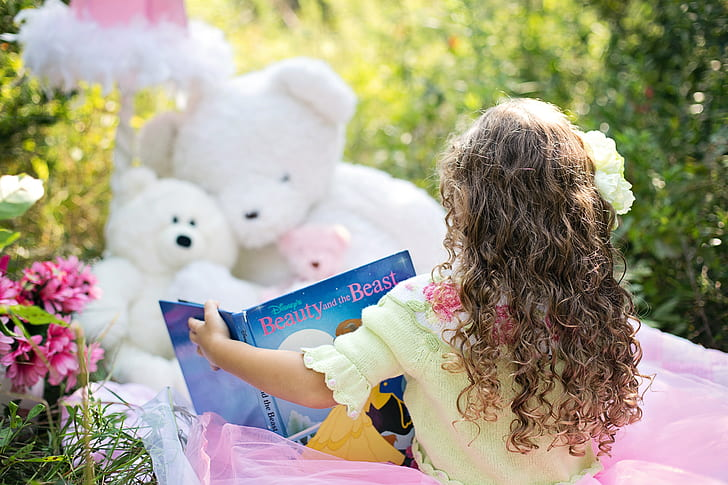 toddler girl seats in front of white teddy bears holding book
