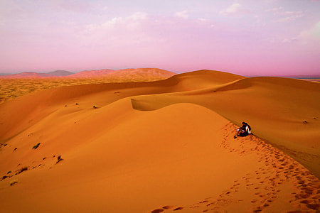 Two people sit in the sandy desert in Morocco, Africa