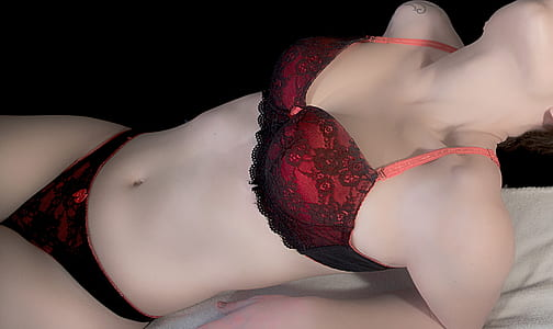 woman laying on bed wearing red-and-black floral lace bra and pantie set