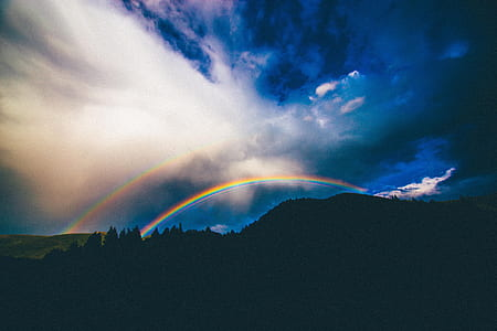 silhouette photography of mountain with rainbows