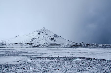 landscape photography of snow hill under cloudy sky