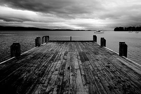grayscale photography of dock bridge near ocean