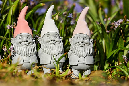 selective focus photography of three gnome figurines