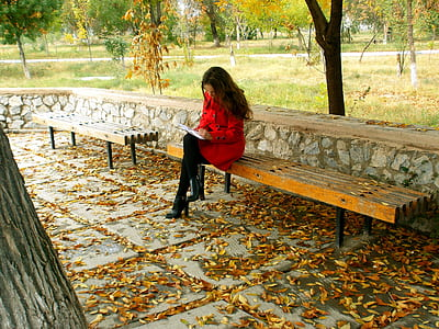 woman in red coat sitting on a bench