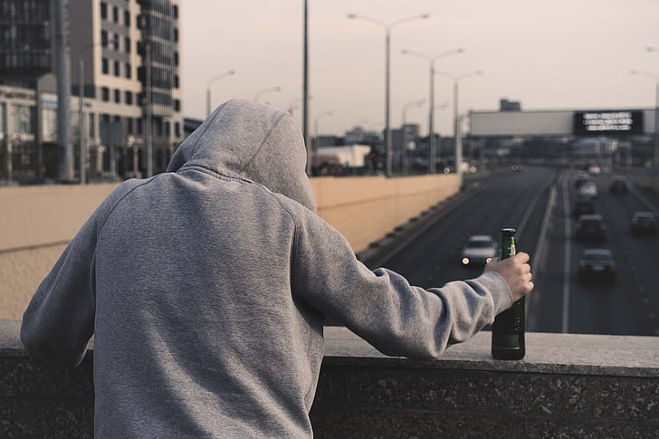 person wearing gray pullover hoodie holding bottle
