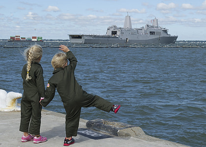 two children waving at the ship