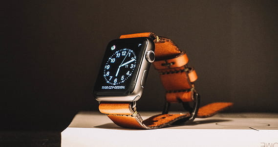 silver case Apple Watch with brown straps on countertop