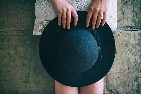 woman holding black sun hat