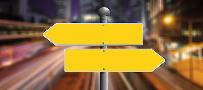 selective focus photography of two yellow arrow signages