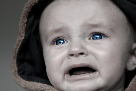 grayscale photo of baby crying wearing brown hoodie