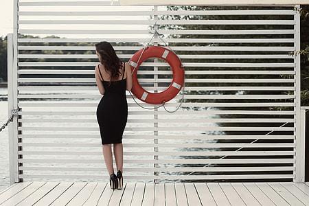 Woman with long hair wearing a black fashion dress