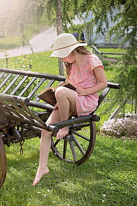girl wearing white hat and pink floral short-sleeved dress sitting on brown wooden trailer while holding book