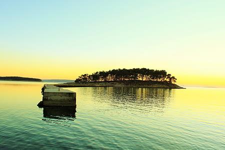 island with tree facing horizone