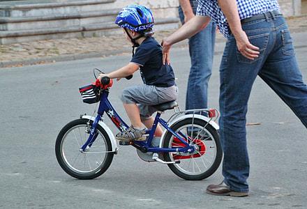 boy riding bike while man pushing him