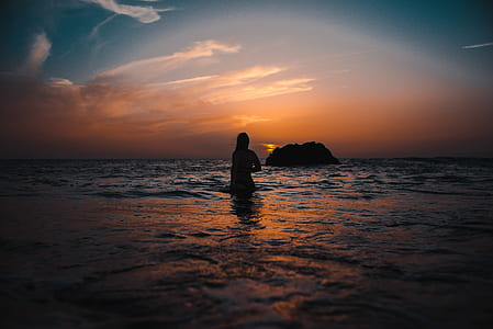 Silhouette of Woman On Ocean During Sunset
