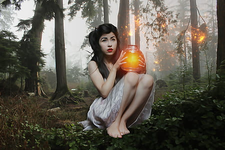 woman holding glowing jar sitting in forest