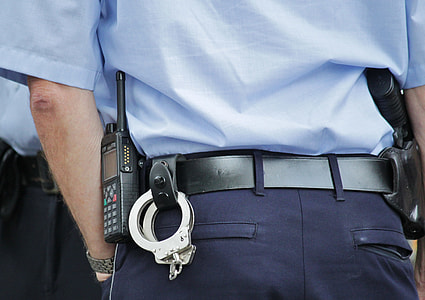 person wearing cop uniform with handcuff and two-way radio