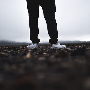 person in black pants wearing white Converse low top sneakers in tilt shift photography
