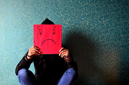 person in black hoodie and blue denim bottoms holding square red paper with sad face drawing