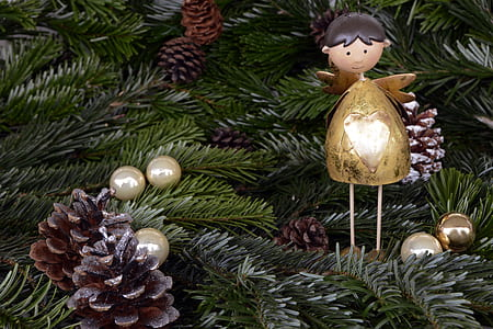 angel, pinecone and bauble ornaments hanged on christmas tree
