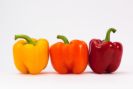 three bell peppers on white surface