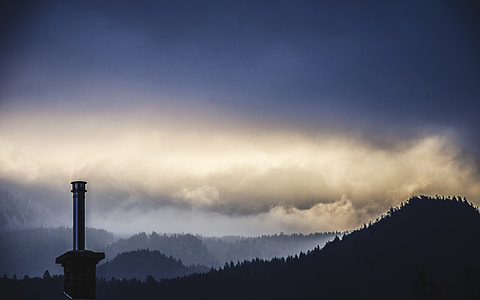 silhouette of light tower and mountain during cloudy day