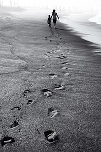 photo of boy and girl foot prints on sand