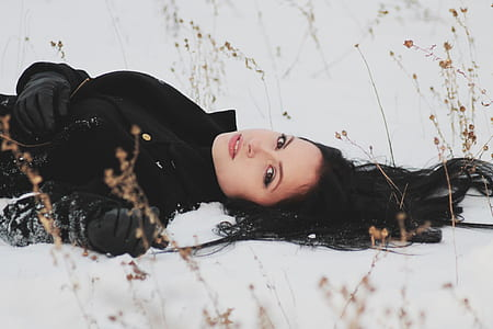 woman wearing black coat laying on snow field