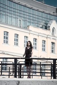 woman wearing black sleeveless dress on concrete bridge