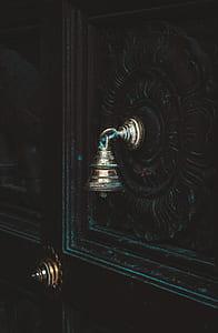 black wooden door with gray bell