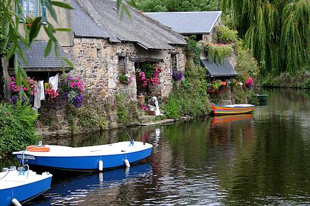 blue boat docked near gray stone house