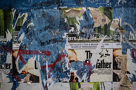 Wide angle shot of torn flyers and posters on a wall in Brooklyn, New York City