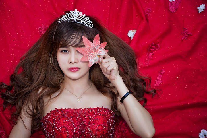 woman in red strapless sequined dress holding red petaled flower