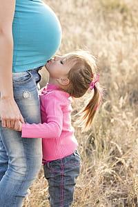 girl kissing woman's tummy