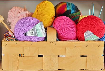 assorted-color yarns on brown basket
