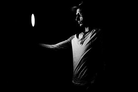 man holding round light inside dark room