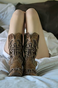 person wearing brown leather x-toe cowboy boots lying on bed