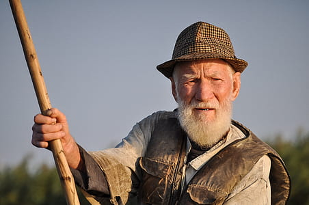 Man Wearing Hat Holding Wooden Rod Under Gray Sky