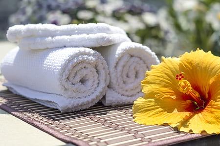three white towels near yellow flower
