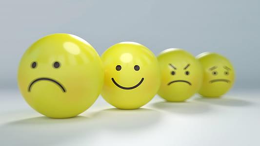 four assorted emoji balls focusing on smiley emoji
