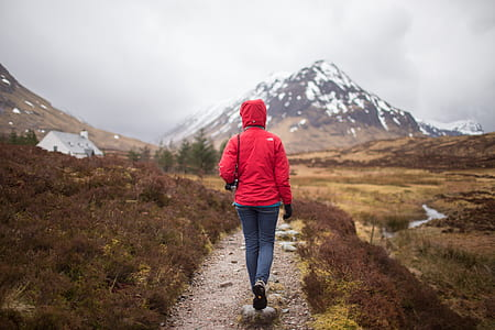 person in red hooded jacket and blue denim jeans walking near mountain covered by snow during daytime