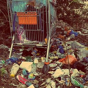 gray shopping cart on pile of garbage