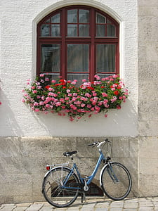 blue commuter bike parked on concrete building