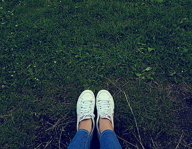 person wearing white low-top sneakers  standing on green grass
