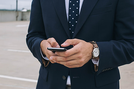man in  blue suit jacket  and blue necktie holding smartphone during daytime
