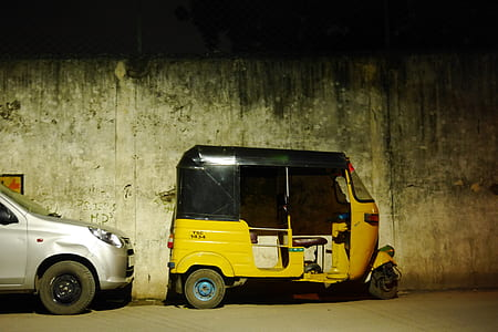 yellow and black auto rickshaw parked by gray concrete wall